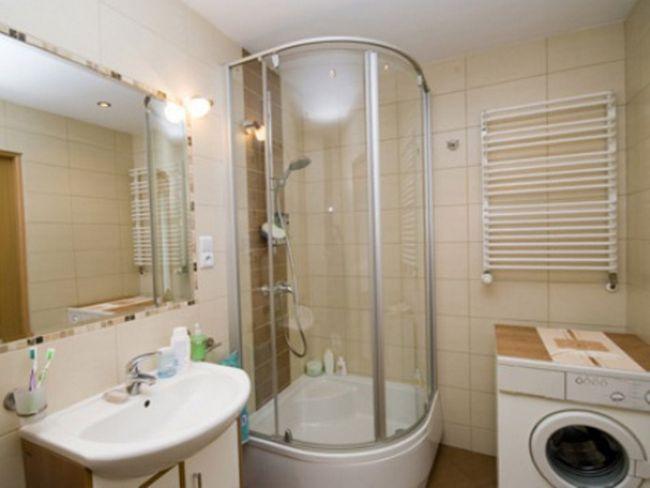 Дизайн ванної кімнати з встановленої в кутку душовою кабіною.